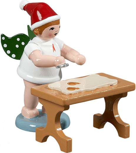 Christmas angel with cookie cutter at the table, with cap